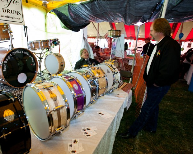 St. John Town Council President Mike Forbes, right, talks drums with Beat Boogie entrepreneur Steve Crabtree at the St. John 175th Anniversary Festival last fall. Steve handcrafts drum sets locally for famous musicians.